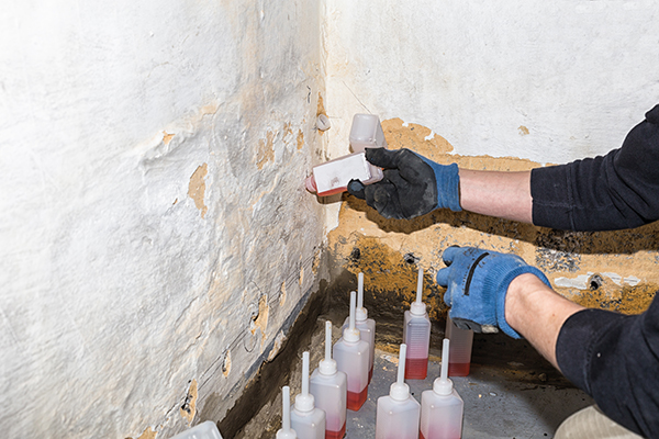 Wall being damaged by dampness resulting in peeled of plaster and color. In the bore holes in the wall synthetic resin is injected to establish a dampness barrier.