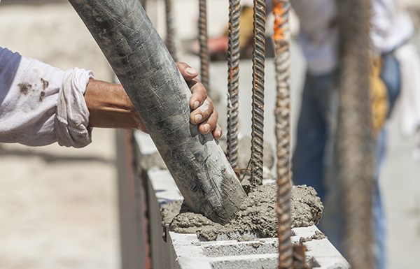 A construction worker directs the flow of wet cement into a cinder block wall on a job site.